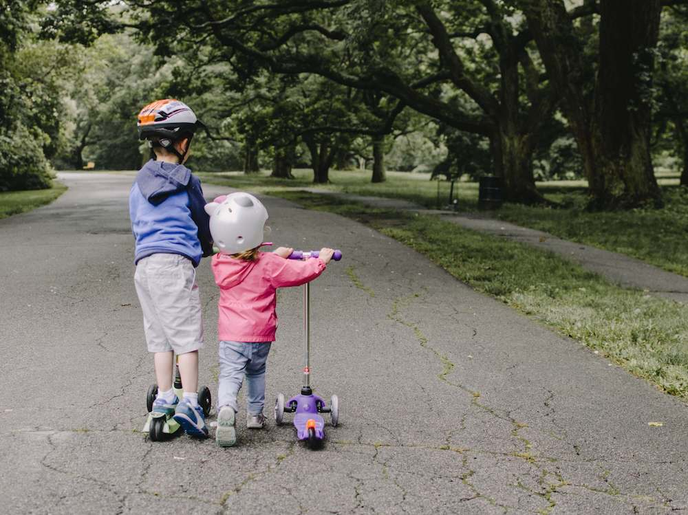 Young kids ride their 3 wheel scooter in a park